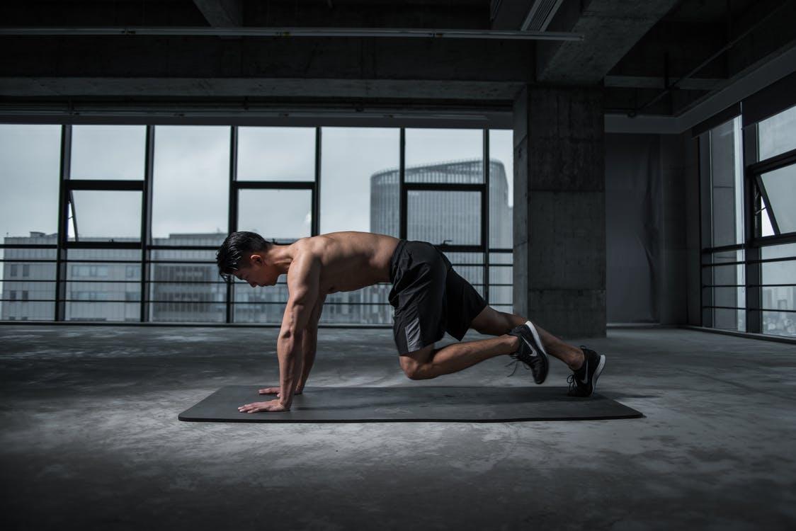 mand står i planke i fitnesscenter